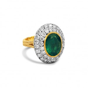 An Oval Emerald mounted in 18k white and yellow gold with G VS diamonds