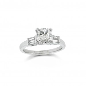 A cushion cut diamond weighing 1.20 carats mounted in 18K white gold with baguette side stones