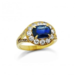An Oval sapphire mounted in 18k yellow gold with G VS quality diamonds