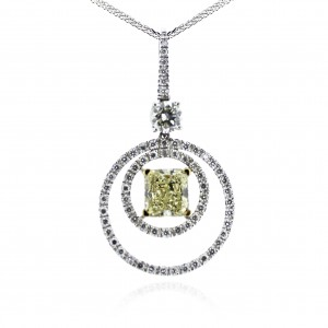 A 2.02 carat Radiant cut fancy yellow diamond mounted with diamonds in 18k White gold